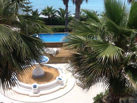 Vista di un giardino con una fonte piena di sabbia e una piscina di fronte al mare,circondata da pavimento in legno e protetta da legno