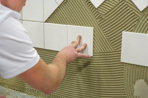 tecnico durante posa piastrelle di ceramica