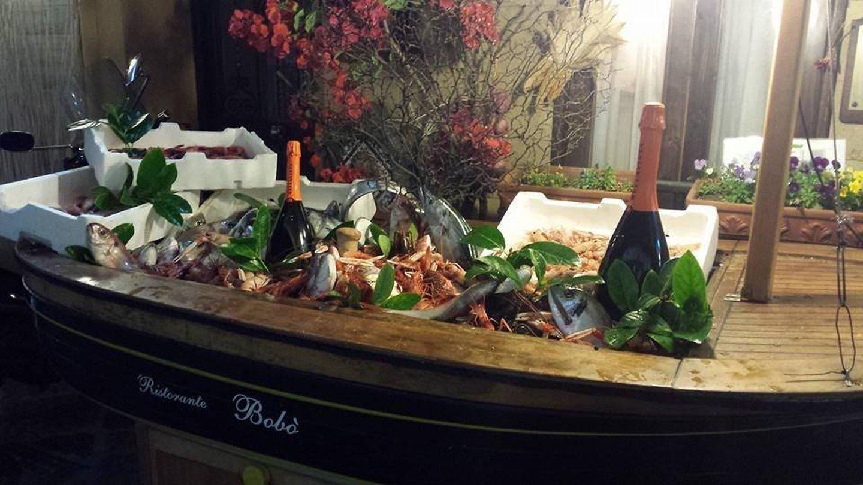 superficie in legno a forma di barca con vino e pesce che pubblicizzano il RISTORANTE BOBO