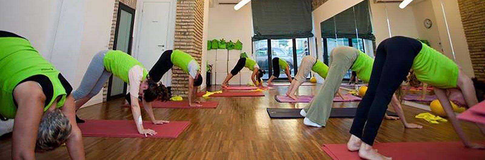 un gruppo di persone con una divisa verde chinate con le mani appoggiate su dei tappetini da ginnastica mentre svolgono degli esercizi