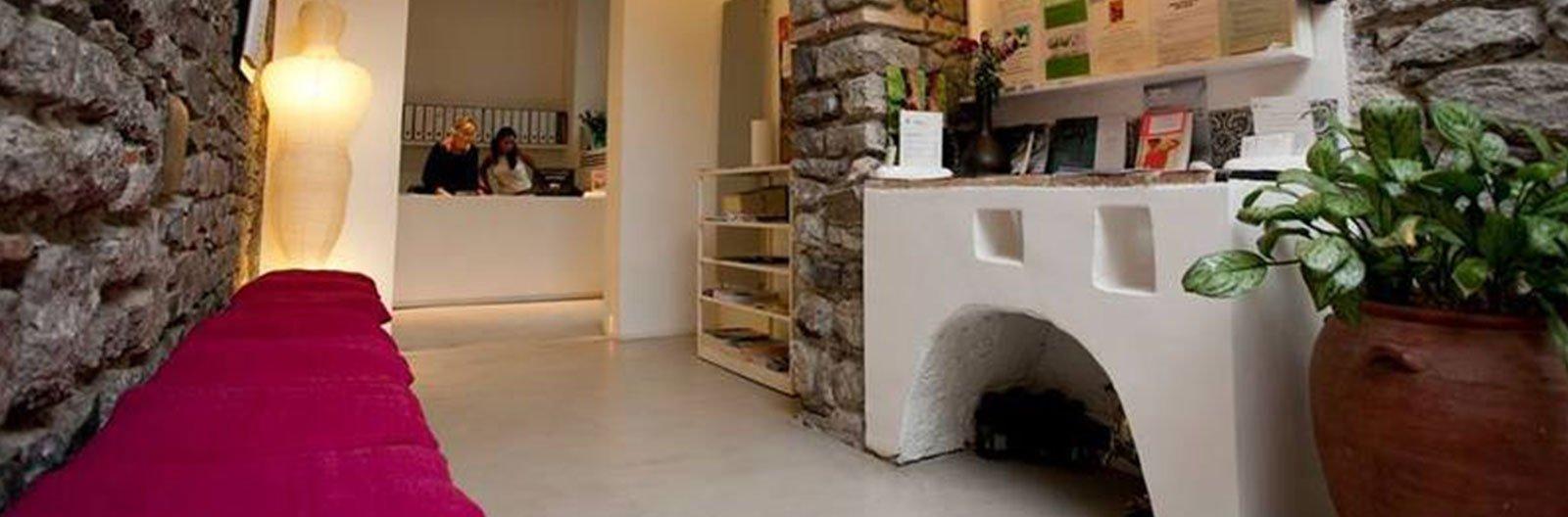 una sala con sulla destra una struttura in marmo con dei fogli appesi al muro e altri oggetti, un vaso con una pianta e in lontananza due donne dietro a un bancone
