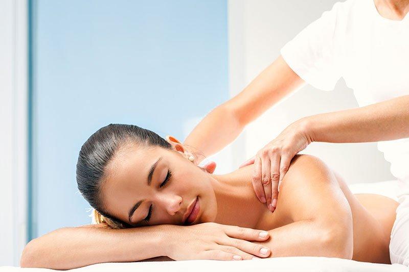 una donna senza vestiti sdraiata su un lettino e dietro delle mani che le massaggiano la schiena