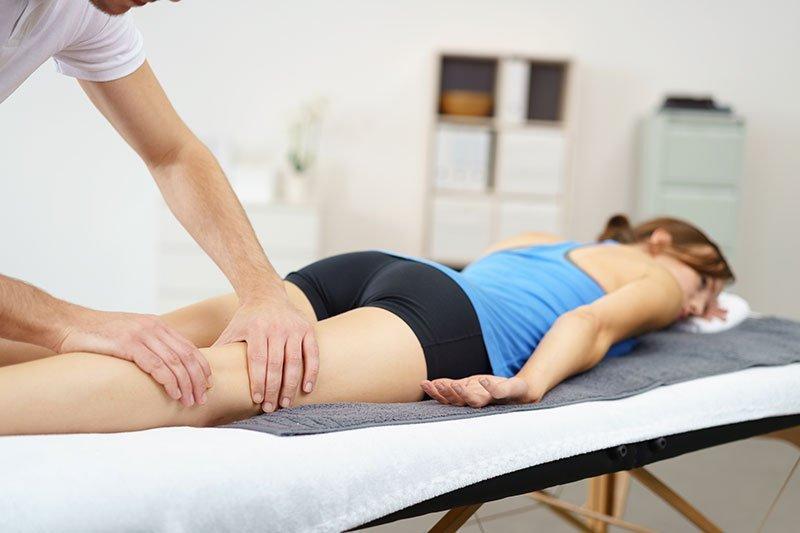 una ragazza con un top azzurro e dei pantaloncini neri sdraiata a pancia in giù su un lettino e un massaggiatore che le massaggia le gambe