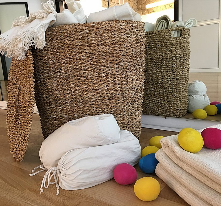due cestini di paglia con dentro della biancheria e accanto delle sacche bianche, asciugamani piegati e delle palline di stoffa di diversi colori