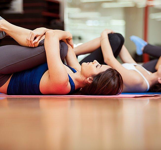 due donne, una vestita con un top blu e l'altra bianco mentre svolgono degli esercizi di stretching sdraiati a pancia in su