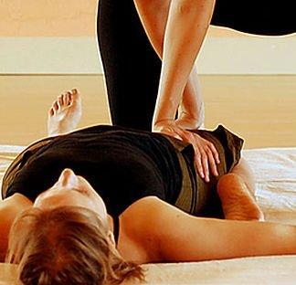 una donna vestita di nero sdraiata a pancia in su mentre fa degli esercizi di stretching delle gambe