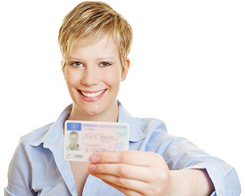 Donna sorridente che mostra la sua patente