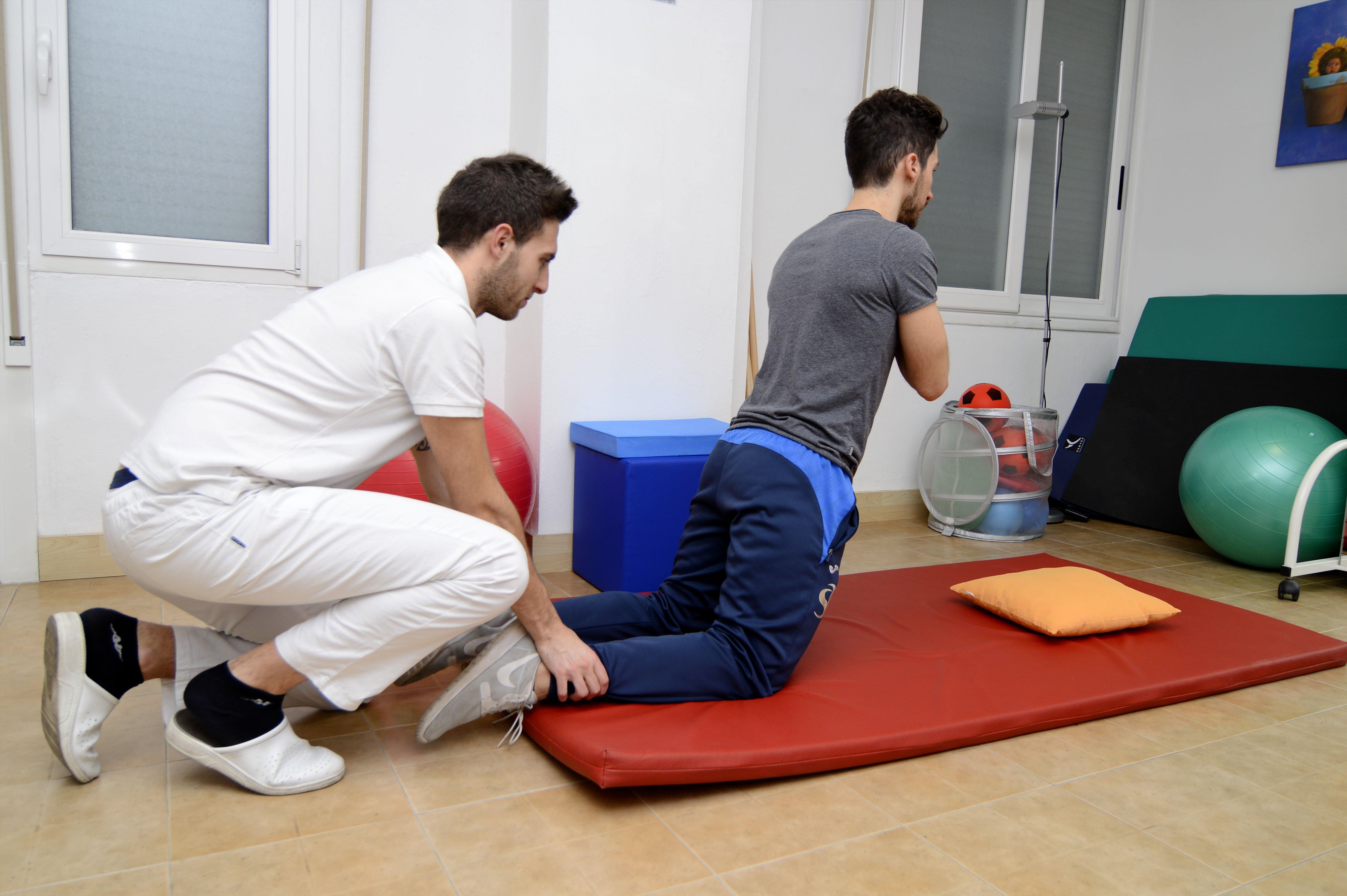 Fisioterapista tiene le gambe di un paziente che fa un esercizio