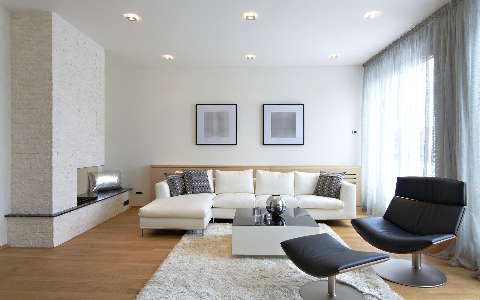 un divano angolare di color bianco e una poltrona di color nero