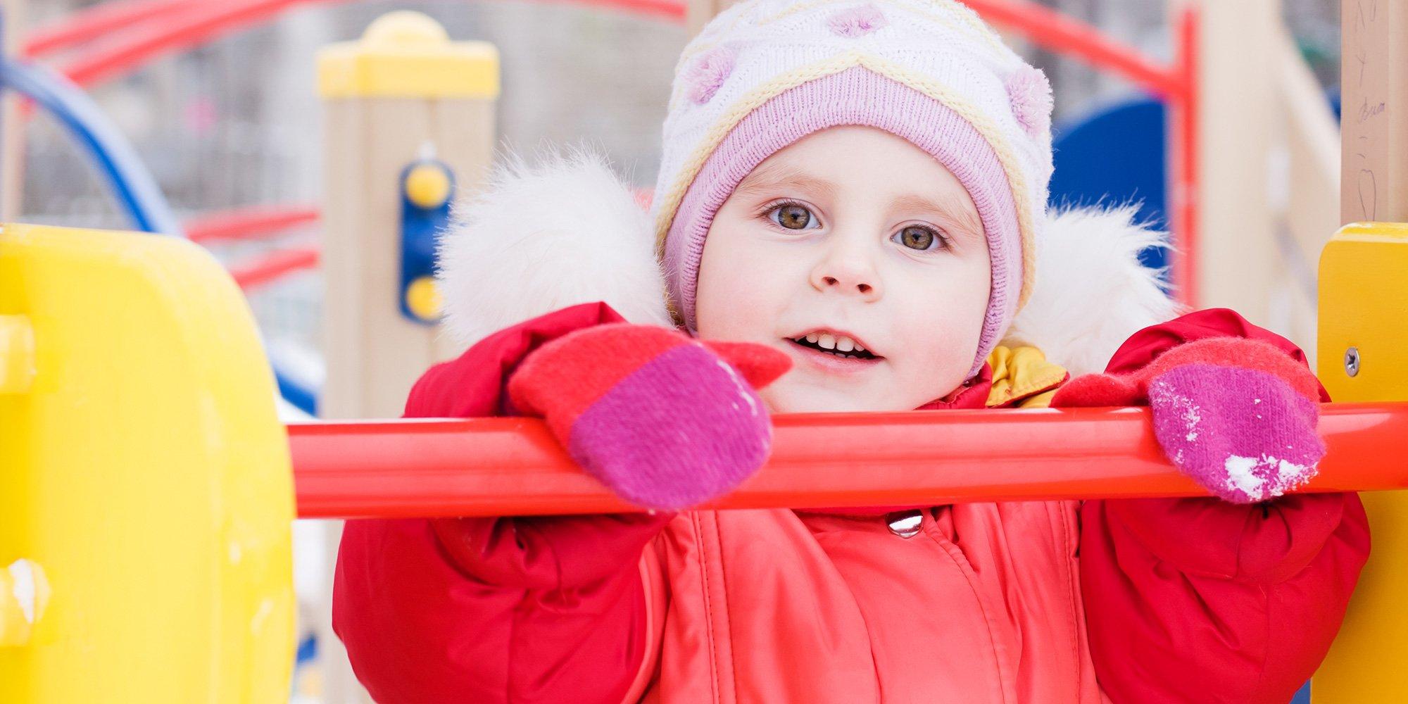 Bambino felice gioca fuori della casa in giacca rossa