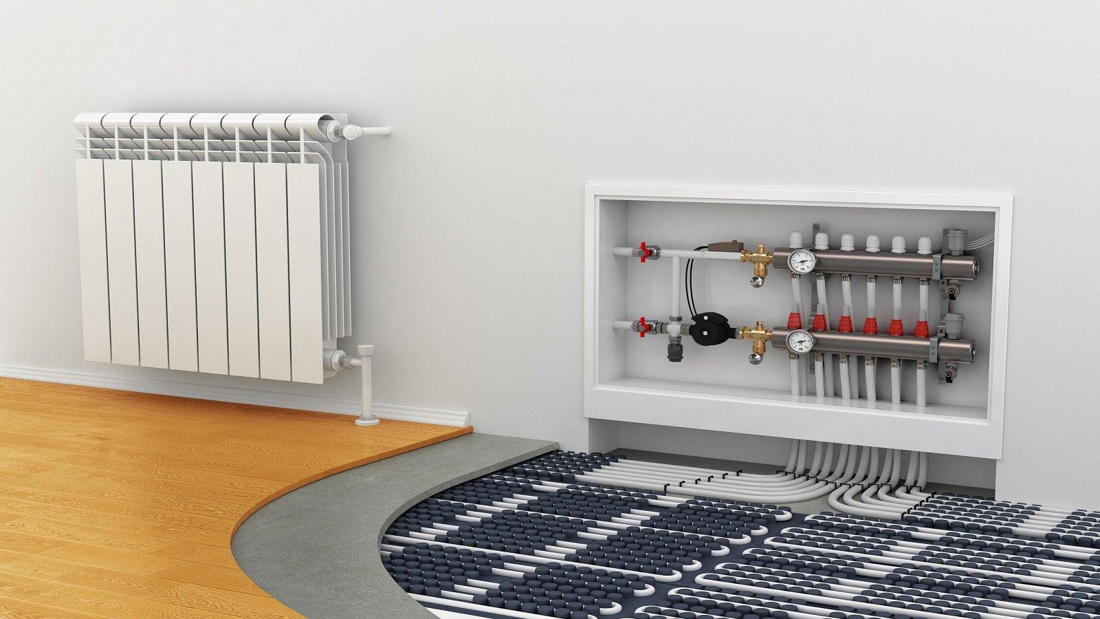 un calorifero e accanto i tubi a vista di un impianto termoidraulico