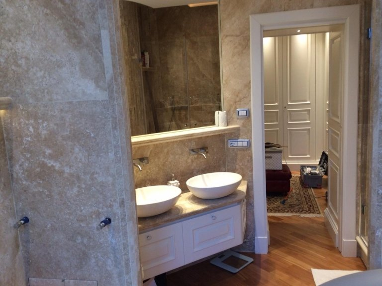 lavabi in un bagno, pavimento in legno , parete in marmo e arredamento in marmo o granito di una casa