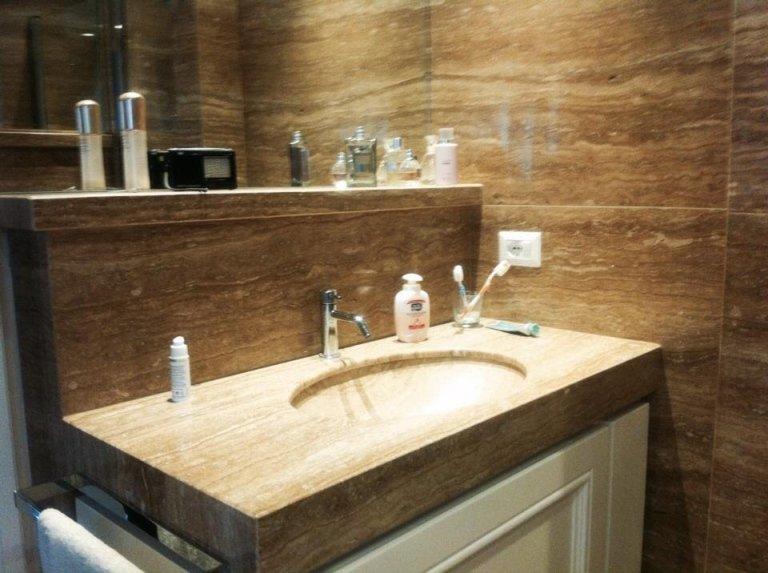 moderno lavabo in marmo in un bagno in una unità di vanità di legno con prodotti da bagno e asciugamani freschi