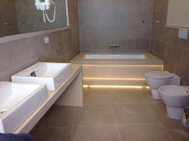 lavabi, bide e una vasca in un bagno con pavimento e parete in marmo