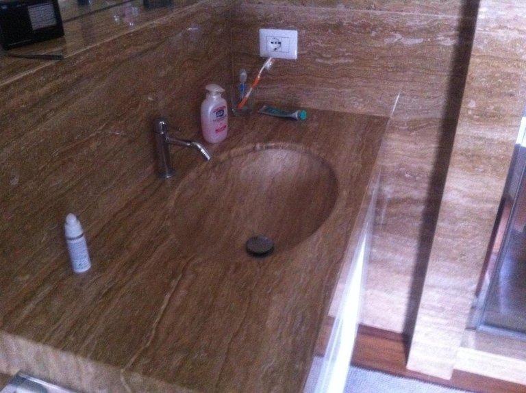 vista laterale di lavabo in marmo in una unità di vanità di legno con prodotti da bagno