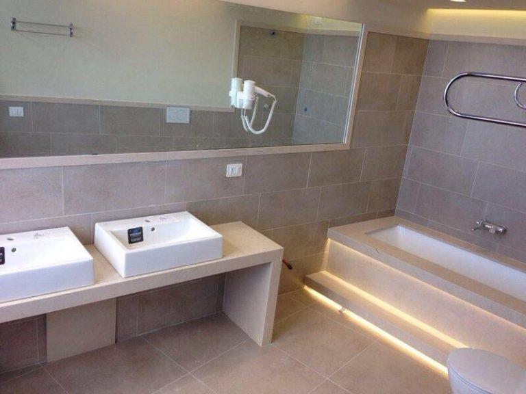 lavabi e una vasca in un bagno con pavimento e parete in marmo