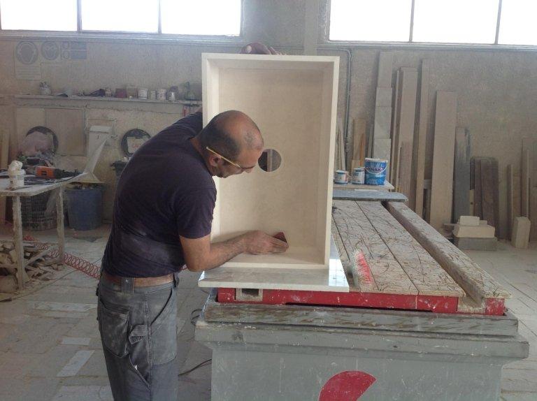 operaio mentre lavora su una vasca in marmo in un magazzino