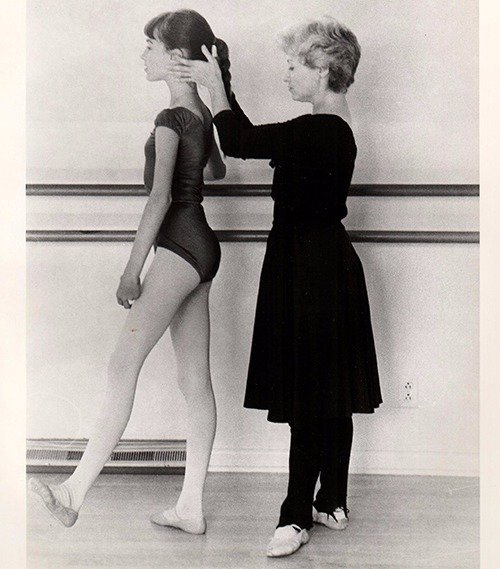 Professional ballet dancer teaching a young girl the correct posture for ballet in Columbia, MO