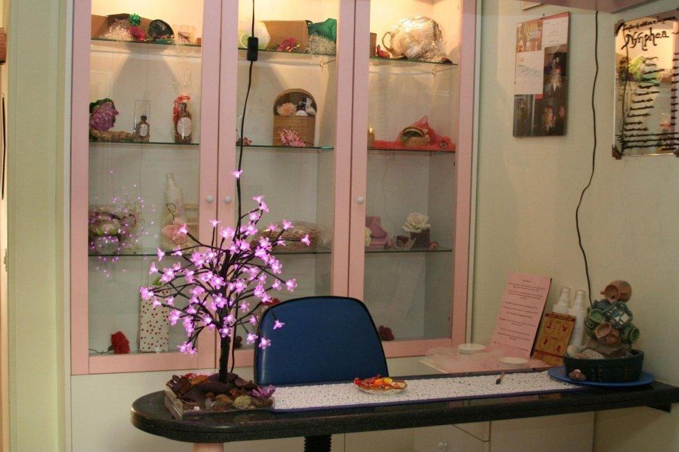 una scrivania con una sedia blu e dietro un armadietto in vetro di color rosa