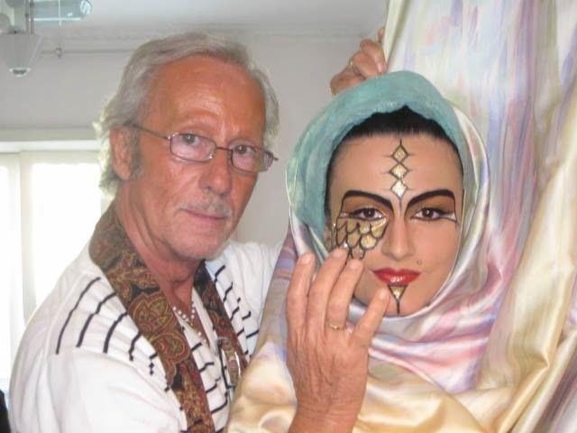 un signore è accanto una ragazza con il viso truccato di color oro con una pittura facciale