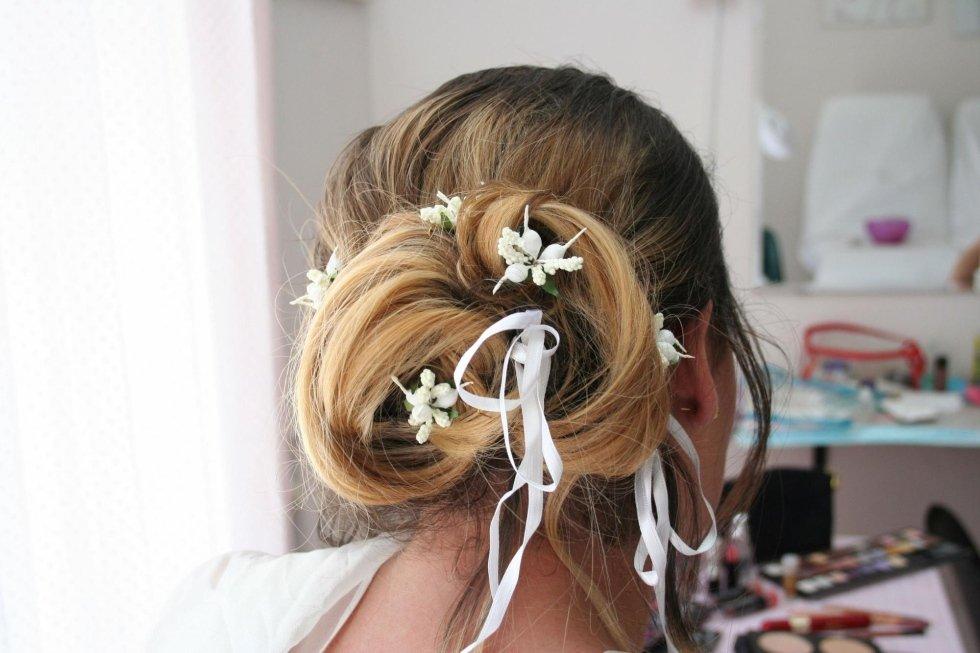 i capelli di una donna visto da dietro con meches bionde e un nastro bianco con dei fiori