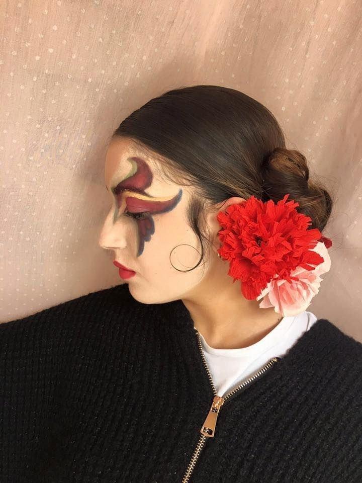 una ragazza con una pittura facciale di color rosso e giallo su un occhio e dei fiori rossi sui capelli