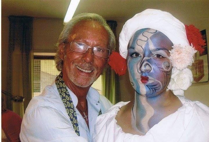 un signore accanto a una ragazza con una pittura facciale azzurra,rossa e bianca