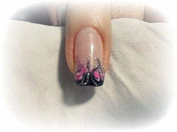 un'unghia con uno smalto rosa e nero a disegni