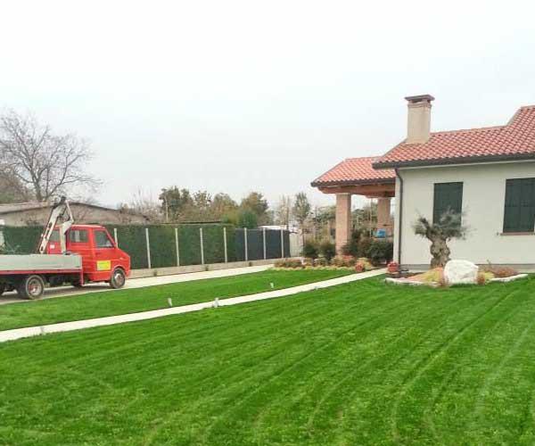 un prato appena tagliato in un giardino, sulla sinistra un camion rosso da lavoro e davanti una