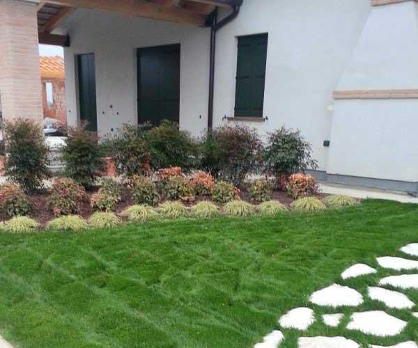Vista di un atrio di un villa, aiuola con piante, prato verde e una camminata in sassi bianchi