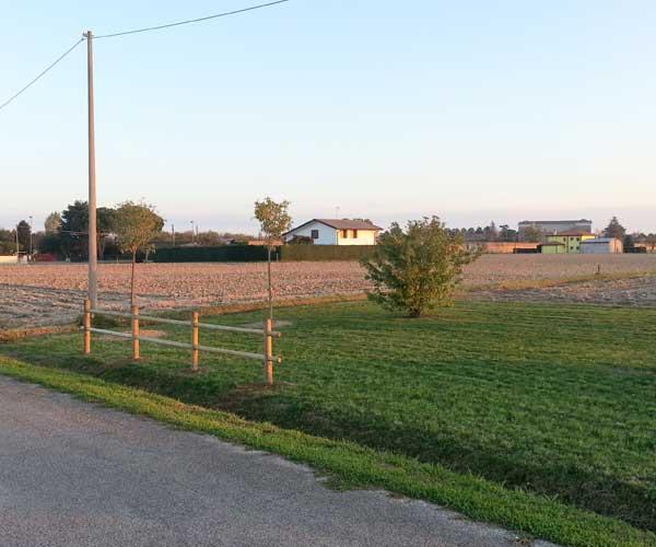 un terreno con un prato verde e delle ville visto da lontano