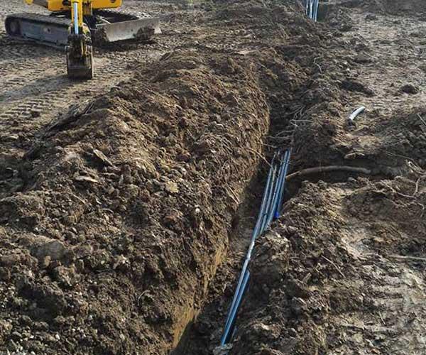 Un terreno scavato e dei tubi  blu a vista