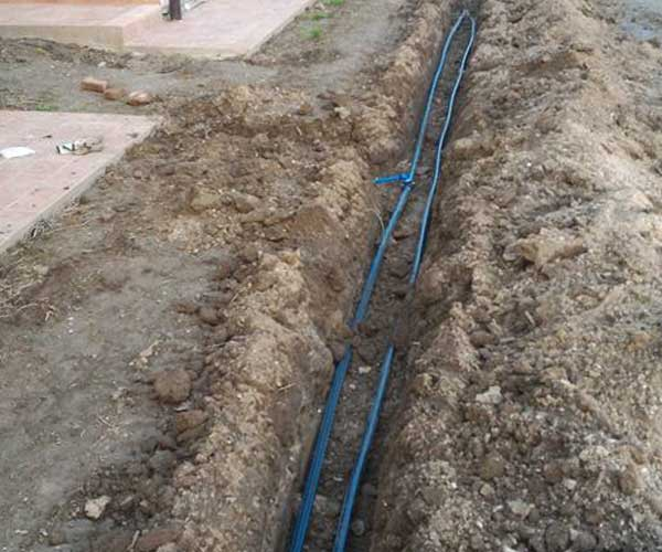Un terreno scavato e due tubi blu dell'irrigazione