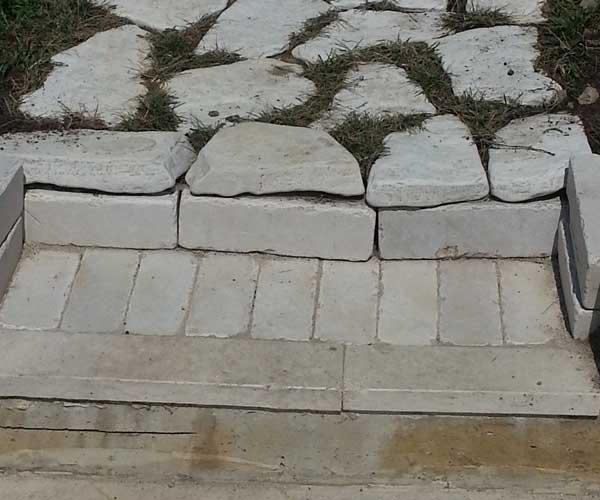 Vista di una camminata in sassi bianchi nel prato che porta a una pavimentazione realizzata con mattoni grigi