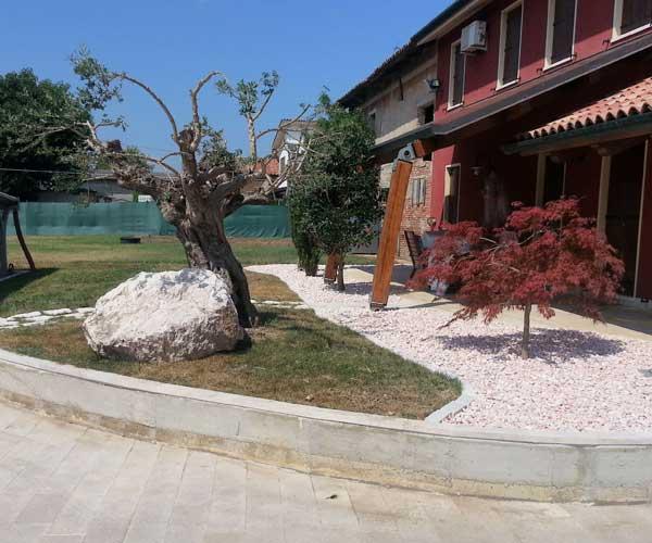 Vista di una villa con la facciata in color bordeaux, aiuole realizzate con sassi bianchi e rosa con degli alberi in mezzo