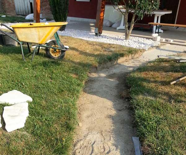 Vista di una camminata in sabbia e prato su due lati che porta alla villa e una cariola gialla nel prato