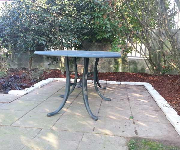 Una tavola da esterno di color grigio e alberi intorno