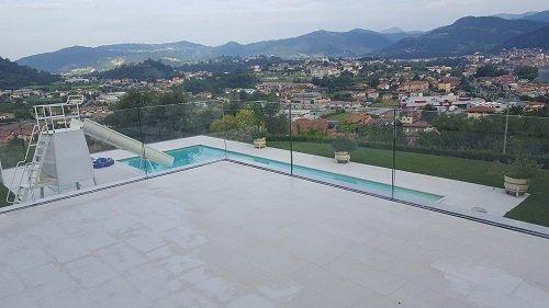 una terrazza con parapetti in vetro e vista di una città