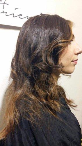 donna girata di lato con capelli lunghi e mossi
