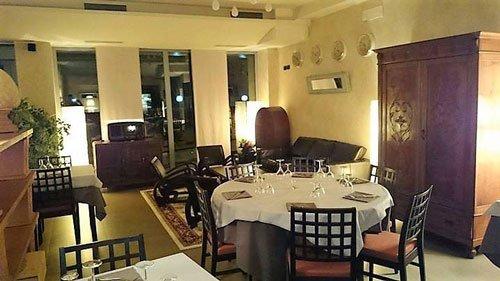sala interna del ristorante con tavoli apparecchiati e sedie