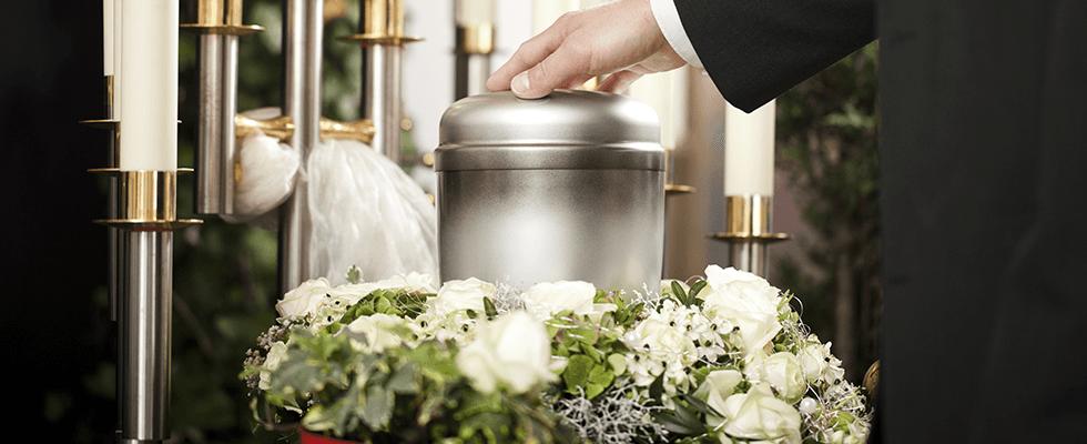 persona che tocca urna posta al centro di una corona di fiori
