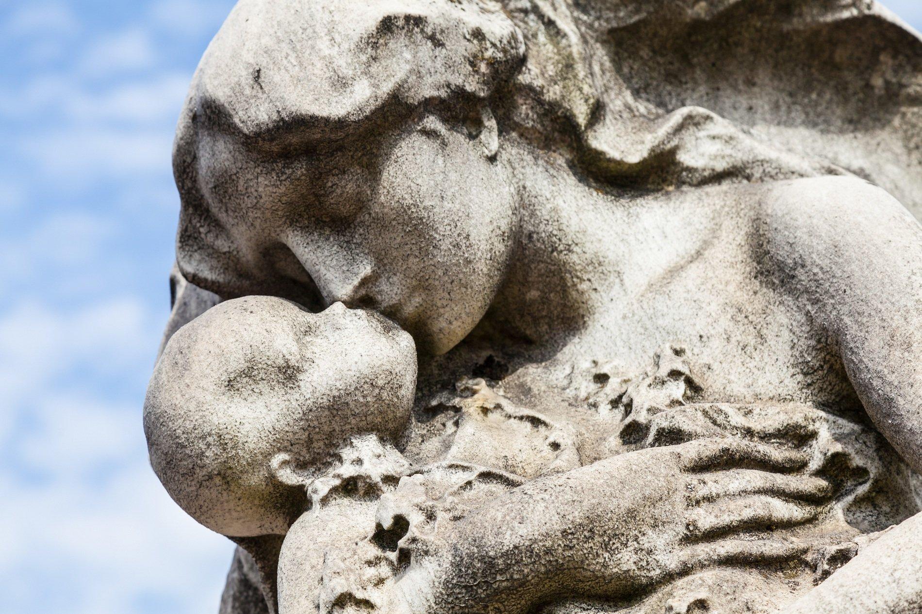 Statua di pietra di una madre che besa a suo figlio