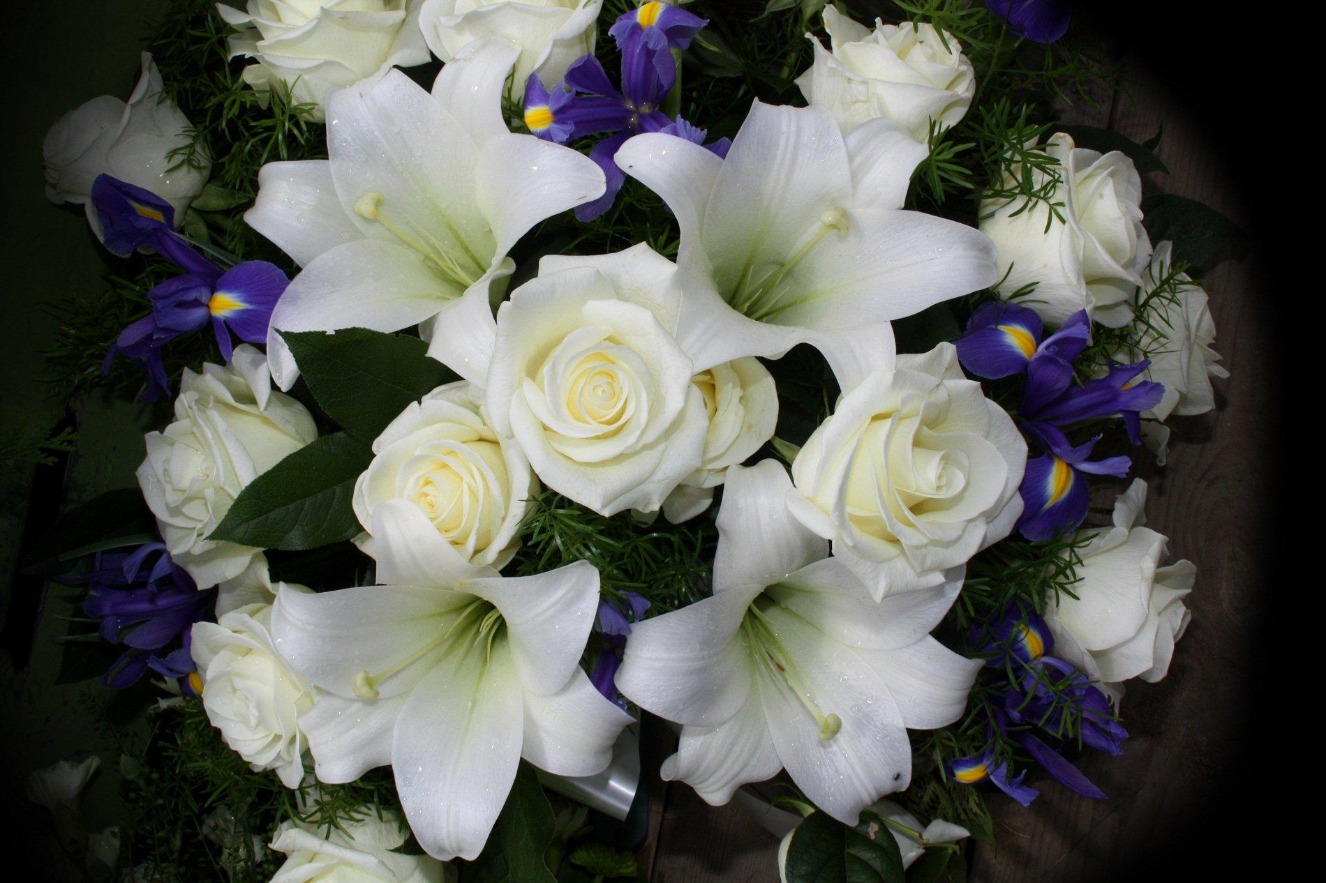 Ornamento floreale di iris violetti,gigli e rose bianchi
