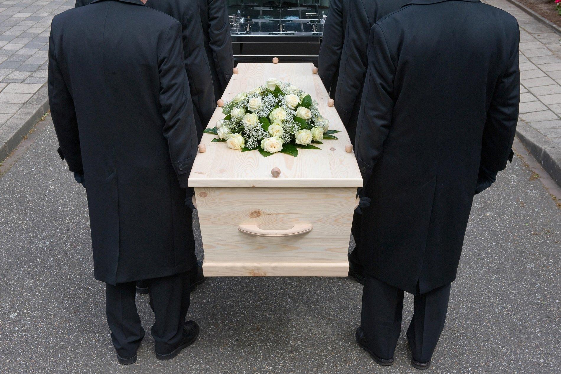 Sei uomini portando una bara in legno chiaro con rose bianche sopra ,al carro funebre