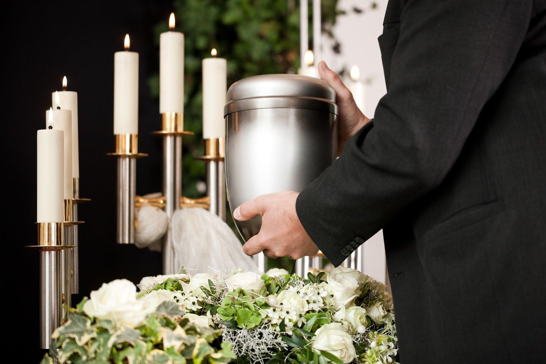 Uomo collocando sotto una urna sui fiori bianche accanto alcuni candele