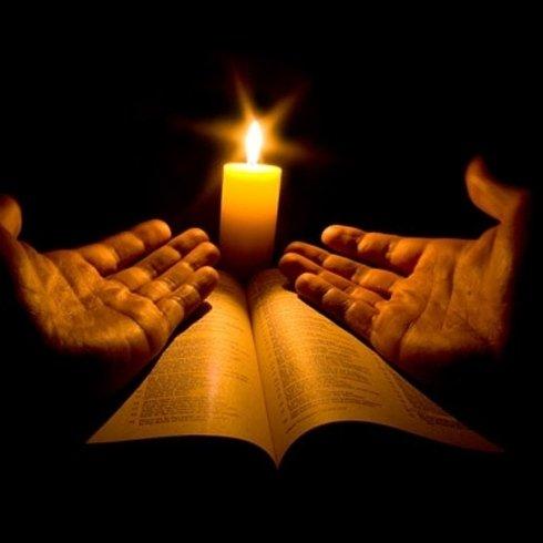 mani in preghiera su una Bibbia con una candela