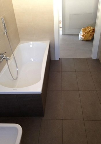 un bagno con una vasca e pavimento in piastrelle scure