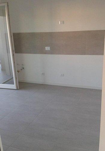 una stanza con un pavimento di color grigio e un muro di color bianco e grigio