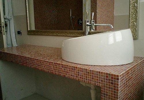 un bagno con uno specchio al muro e un lavabo moderno