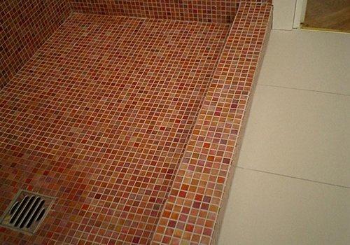 un box doccia con pavimento in piastrelle arancioni e rosa